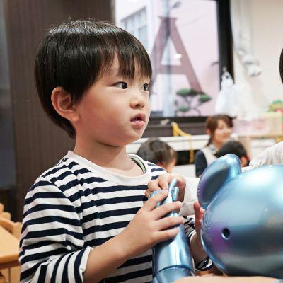 Kaksi lasta pitää kiinni sinisen, nallea muistuttavan robotin kädestä.