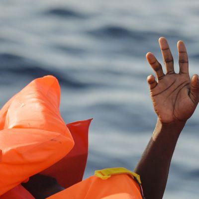 Maahanmuuttaja istuu kumiveneessä Välimerellä.