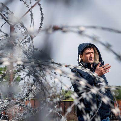 Maahanmuutaja Serbian ja Unkarin rajalle pystytetyn piikkkilanka-aidan luona.
