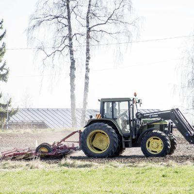 Traktori pellolla toukotöissä.