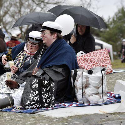 Ihmiset juhlivat vapunpäivää koleassa säässä Kaivopuistossa Ullanlinnanmäellä 1. toukokuuta.