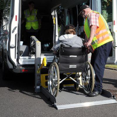 Pyörätuolissa istuvaa henkilöä autetaan auton kyytiin.