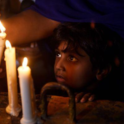 Srilankalainen lapsi katselee muistokynttilöitä.