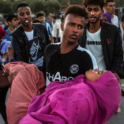 Siirtolaismies kantaa naista turvaan mellakan keskeltä.