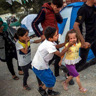 Maahanmuuttajat suojautuivat poliisien kyynelkaasulta Morian pakolaisleirillä Lesboksen saarella Kreikassa 29. syyskuuta.