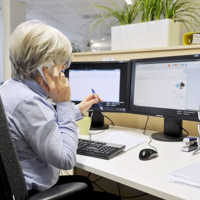 harmaatukkainen nainen tietokoneen ääressä