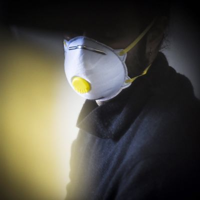 Mies käyttää FFP2 -hengityssuojainta