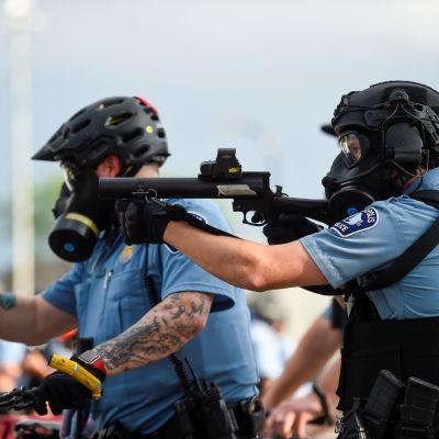 Poliisit tähtäävät aseella mellakoitsijoita Minneapoliksessa, Minnesotan osavaltiossa Yhdysvalloissa.