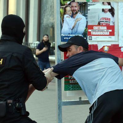 Mellakkapoliisi pidättää opposition kannattajaa Minskissä Valko-Venäjällä.