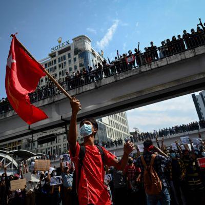 Mielenosoittaja pitää kädessään lippua protestissa Yangonin kadulla.