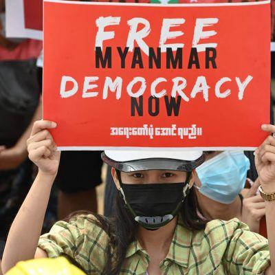 Mielenosoittaja pitelee sotilasvallankaappausta vastustavaa kylttiä Yangonissa.