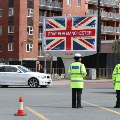 Pray for Manchester -kyltti, etualalla kaksi poliisia.