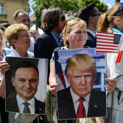 Puolalaisia käsissään Yhdysvaltain ja Puolan presidentin kuvia sekä maiden lippuja.