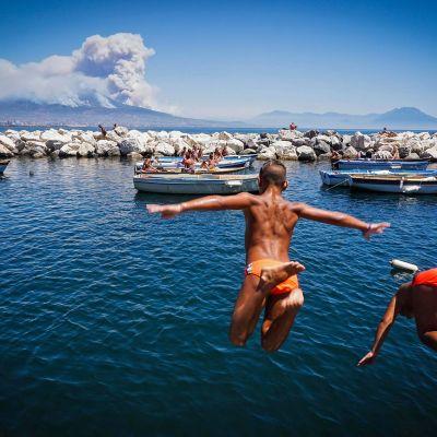 Napolilaislapset hyppivät uimaan samalla, kun Vesuviuksen ympärillä riehuvat metsäpalot savuttivat horisontin Italiassa 11. heinäkuuta.