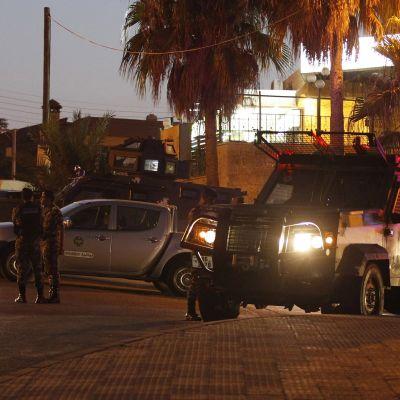 Jordanian turvallisuusjoukot partioivat Israelin suurlähetystön edustalla Ammanissa 23.7. 2017. Kuvassa turvallisuusjoukkojen ajoneuvoja palmujen alla illan hämärtyessä.