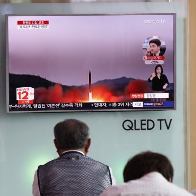 Ihmiset katsovat televisioruutua, jossa kuvaa laukaistavasta ohjuksesta.