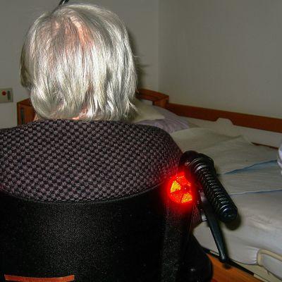 Vanha nainen pyörätuolissa lähellä sänkyä.
