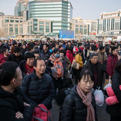 Kuvassa ihmisiä jonottamassa Pekingin rautatieasemalle.