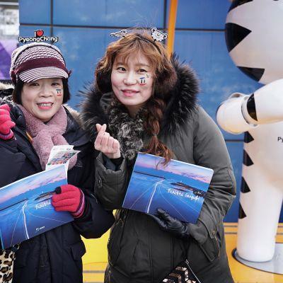 Kuvassa kaksi naista esitteet käsissään Etelä-Korean talviolympialaisissa.