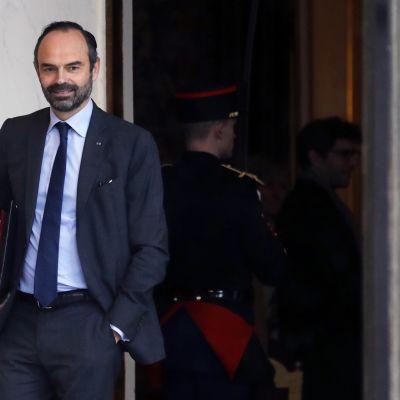 Ranskan pääministeri Edouard Philippe kävelee ulos ovesta asiakirjamappi kainalossaan.