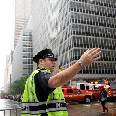 Poliisi ohjaa palomiehiä kohti pilvenpiirtäjää jonka katolle helikopteri teki pakkolaskun Manhattanilla 10. kesäkuuta.
