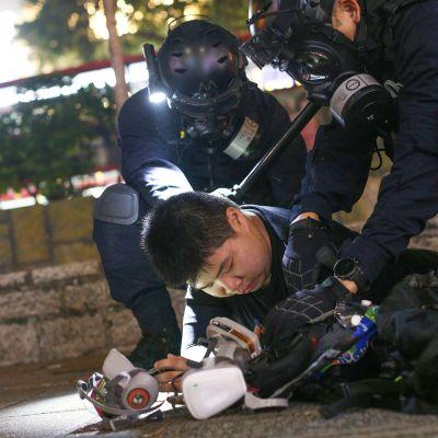 Poliisi pitävät mielenosoittajaa maassa tiukalla otteella.