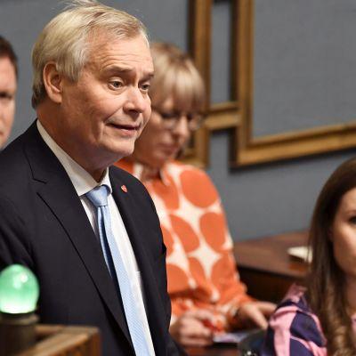 Statsminister Antti RInne talar i plenum 7.11 2019. I bakgrunden syns också ministrarna Ville Skinnari och Aino-Kaisa Pekonen samt Sanna Marin.