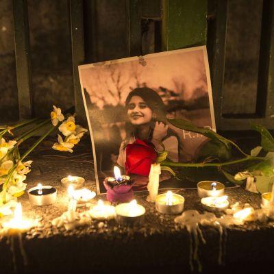 Nuoren naisen kuv on asetettu kiveykselle. Ympärillä on kynttilöitä ja kukkia.