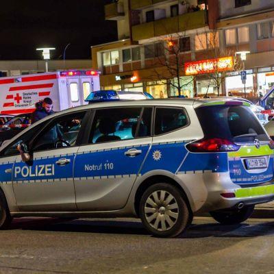 Poliisiauto edustalla. Taustalla ambulanssi ja taloja.