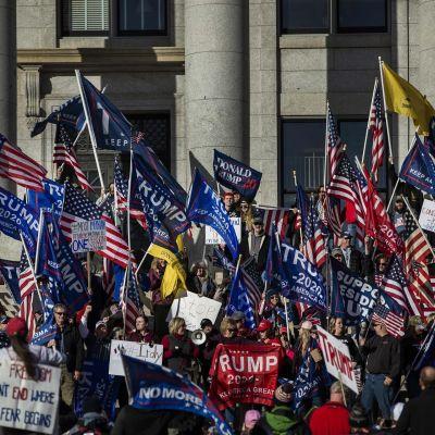Trumpia tukevia lippuja kantava väkijoukko kongressirakennuksen portailla