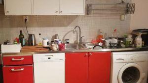 Ostädat kök med flaskor och annat på diskbänken