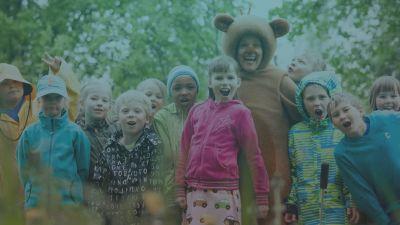Eri lapsia katsoo kameraan, mukana myös karhuksi pukeutunut hahmo.