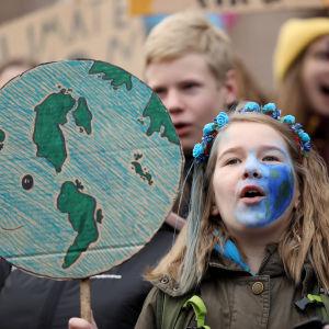 Unga demonstrerar för klimatet på riksdagshusets trappor i Helsingfors.