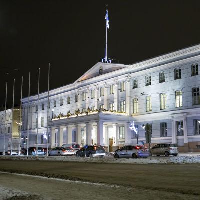 Helsingfors stadshus. Det är en mörk vinterkväll. På gatan utanför stadshuset står bilar på rad. På gatan ligger snö.