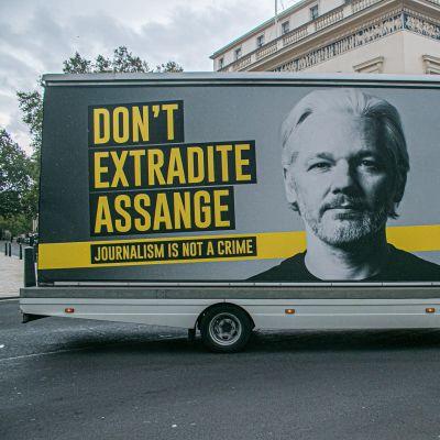 """""""Utlämna inte Assange"""" står det på bussen."""