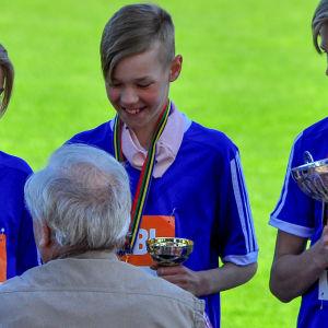 adam på guldpodiet med en pokal i handen och en medalj runt halsen