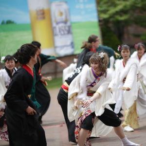 Flera personer iklädda antingen svarta eller vita dräkter. De dansar en japansk dans kallad yosakoi.