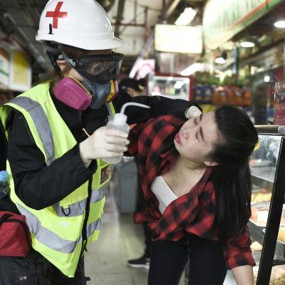 En kvinna som fått tårgas i ansiktet får första hjälpen