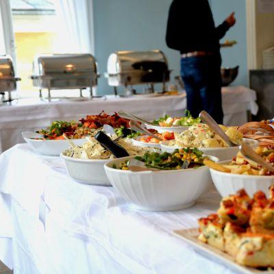 skålar med olika typer av mat i sig på ett buffébord