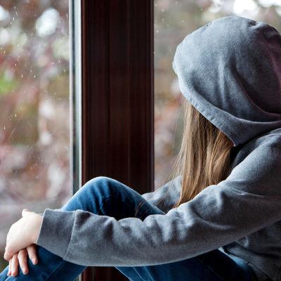 nuori katsoo ulos ikkunasta