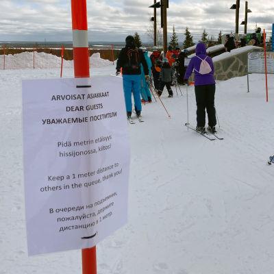 Laskettelijoita Ylläksen hiihtokeskuksen jonossa maaliskuussa 2020. Kyltti kehottaa pitämään metrin turvavälin koronaviruksen vuoksi.