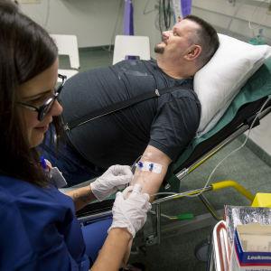 Man får vätska intravenöst genom venkateter. Sjuksköterska håller nålen på plats.