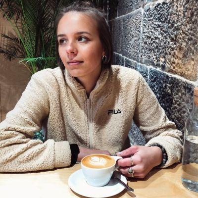En kvinna sitter i ett kafé. Framför sig har hon en kopp kaffe.