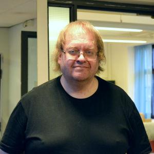 En man iklädd svart t-skjorta och glasögon tittar rakt in i kameran.