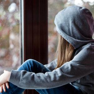 En ung kvinna sitter vid ett fönster och tittar ut.