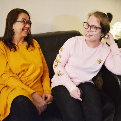 Pirkko Teir och Jasmin Varjo, en fostermamma och en flicka sitter i en soffa