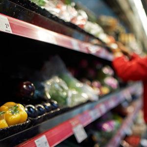 Kvinna sorterar grönsakshylla. I fokus är gula paprikor.