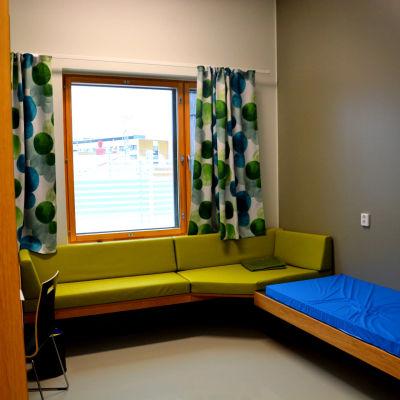 ett rum med en grön soffa, gardiner med gröna detaljer, en säng med ett blått överdrag på