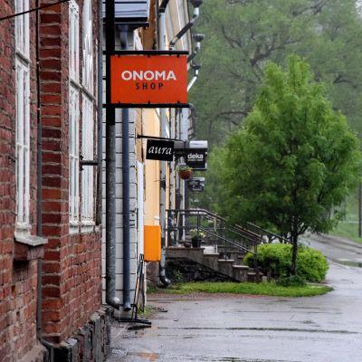 butiksskylt på vägg och gröna träd i bakgrunden
