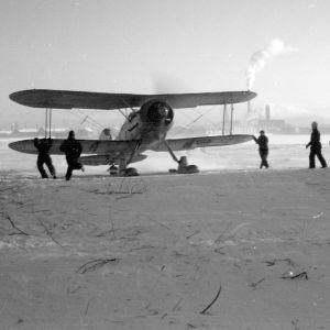 Ruotsalaisen vapaaehtoisjoukon Lentorykmentti 19:n Gloster Gladiator -hävittäjä valmistautuu lennolle, taustalla näkyy Veitsiluodon paperitehdas.